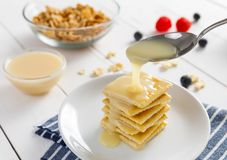 Crackers with condensed milk and fruit Stock Images