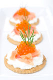 Crackers with cream cheese, salted salmon and red caviar closeup Royalty Free Stock Photos