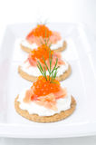 Crackers with cream cheese, salted salmon and red caviar Royalty Free Stock Photography