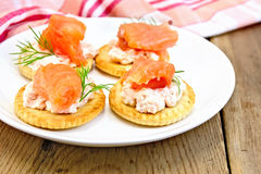 Crackers with cream and salmon on board Royalty Free Stock Images