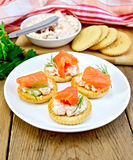 Crackers with cream and salmon in plate on board Stock Photos