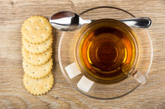 Crackers, cup of tea, lumpy sugar and teaspoon on table Royalty Free Stock Image