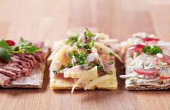 Crackers with different toppings. Three crackers with different savory toppings - closeup Stock Images