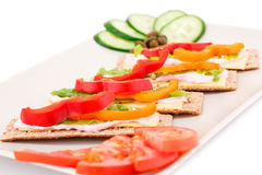 Crackers with fresh vegetables and cream. Crackers with fresh vegetables and cheese on beige plate Royalty Free Stock Photo