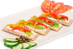Crackers with fresh vegetables and cream. Crackers with fresh vegetables and cheese on beige plate Stock Photos