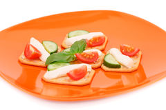 Crackers with fresh vegetables and cream. On orange plate Stock Photography
