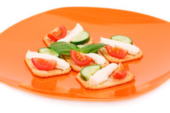 Crackers with fresh vegetables and cream. On orange plate Royalty Free Stock Photos