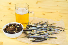 Crackers, a mug of light beer, dried fish on the table. Stock Image