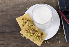Crackers, notebook, pen and a glass of milk on wooden table. Royalty Free Stock Photo