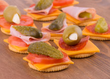 Crackers for snacks, with cheese, tomato, pickle, pepperoni, olives Royalty Free Stock Photo
