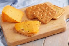 Crackers with spiced gouda cheese and cheese on wooden board stock image