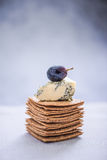 Crackers stack topped with brie cheese and grape Stock Photos