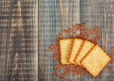 Crackers with sugar and sesame. Lie on a wooden background in chocolate crumbs. There is space for text on the left Stock Photography