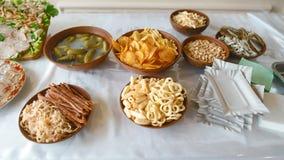 Crackers van variatie de verschillende ongezonde snacks, gezouten noten, stro, het bier en de snacks, chips, pinda's, bacon, komk stock afbeeldingen
