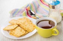 Crackers in plate, sugar bowl, teaspoon on napkin, tea. Crackers in white plate, sugar bowl, teaspoon on napkin, cup of tea on wooden table Stock Photography