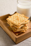 Crackers in wooden tray and glass of milk Royalty Free Stock Images