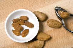 Cracking almonds with a nutcracker Stock Photos