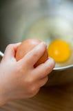 Cracking an egg. In a  bowl Stock Photos