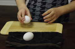 : Cracking egg. Hands cracking white egg on wooden cutting board Royalty Free Stock Photography