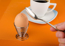 Cracking an egg. Male hand with spoon cracking a hardboiled breakfast egg Stock Image