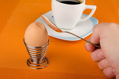 Cracking an egg. Male hand with spoon cracking a hardboiled breakfast egg Stock Photo