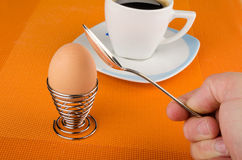 Cracking an egg. Male hand with spoon cracking a hardboiled breakfast egg Stock Photos