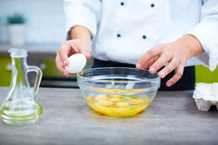 Cracking eggs. A cook cracking eggs in the kitchen Royalty Free Stock Photos