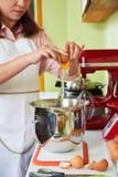 Cracking eggs. Female baker cracking eggs into mixer bowl to make pie dough Royalty Free Stock Image