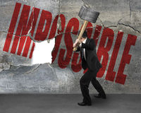 Cracking impossible concrete wall. Businessman cracking impossible concrete wall stock image