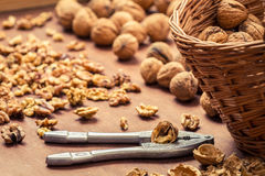 Cracking walnuts on wicker basket Royalty Free Stock Photography