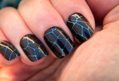 Crackle Nail Art. Perfectly manicured nails with a stamped, crackle nail, art design on a dark shimmer polish stock photography