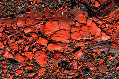 Crackled red ink. Red ink just left on the ground of a factory exposed many years to the rain and the sun Stock Photography