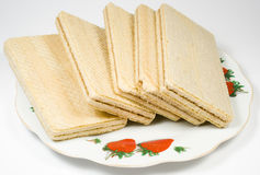 Crackling wafers with a white cream. On a saucer Stock Image
