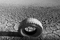 Dried land with cracks and tyre. Cracks on the bottom of a lake after the drought and a tyre Stock Images