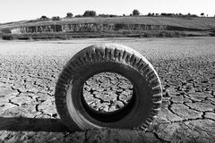 Dried land with cracks and tyre. Cracks on the bottom of a lake after the drought and a tyre Stock Photo