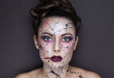 Cracks on face. Beautiful girl with creative make-up for the Halloween party. Bright colors faceart, red lips, stylish hair dress design. Conceptual art broken Royalty Free Stock Photo