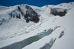 Cracks in the glacier with view to snow high mountains in the sunny day. In Altaj, Russia at the summer stock images