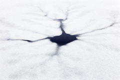 Cracks and hole in ice on pond Royalty Free Stock Photography