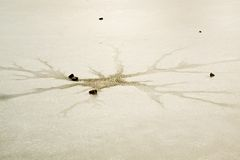 Cracks and hole in ice on pond, dark ice in hole and stone around. Royalty Free Stock Photography