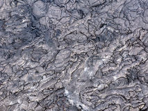 Cracks and shapes emerge from this close up portion of black solidified lava on the island of Hawaii Royalty Free Stock Photos