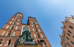 Cracow (Krakow)- Poland- gothic Mariacki Church. Brick gothic Saint Mary s Basilica-Mariacki church and secession house -Cracow, Poland - clock ticking World Royalty Free Stock Photos