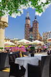 Cracow, Poland- cafe in Cloth Hall overlooking Saint Mary s church Stock Photo