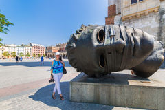 Cracow-Poland-Mitoraj sculpture and woman tourist Royalty Free Stock Photography