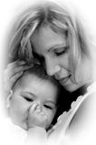 Craddlling her baby. Young mother craddles her infant and lovingly strokes her head.  Child sucks her thumb and lays her head on her mothers chest Stock Images