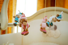 Cradle. Soft toys hangings above a cradle in a nursery, lighted up light from a window Royalty Free Stock Photography