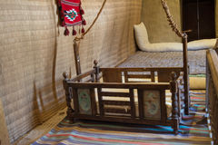 Cradle for babies in the ancient arabian hut. Wooden cradle for babies in the ancient arabian house royalty free stock image