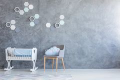 Cradle and chair in nursery. White cradle and grey chair standing against an empty wall in a nursery room interior Stock Photography