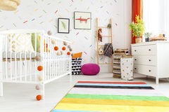 Cradle with colorful balls. White wooden cradle with colorful balls in modern baby room Stock Images