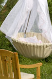 Cradle in the garden. Chair nearby Royalty Free Stock Images