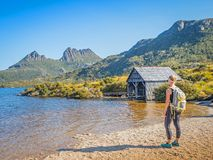 Cradle Mountain and Dove Lake. CRADLE MOUNTAIN - LAKE ST CLAIR NATIONAL PARK, AUSTRALIA - FEBRUARY 24, 2019: An unidentified female hiker looks at the boathouse stock photo